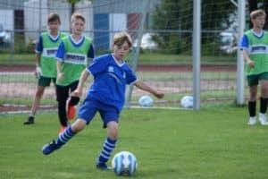 Junge dribbelt mit dem Fußball